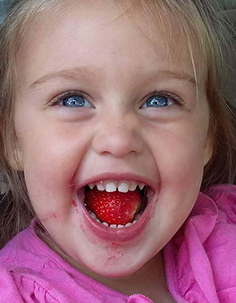 child with strawberry in her mouth.