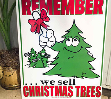 "A sign to ""remember we sell Christmas trees."""